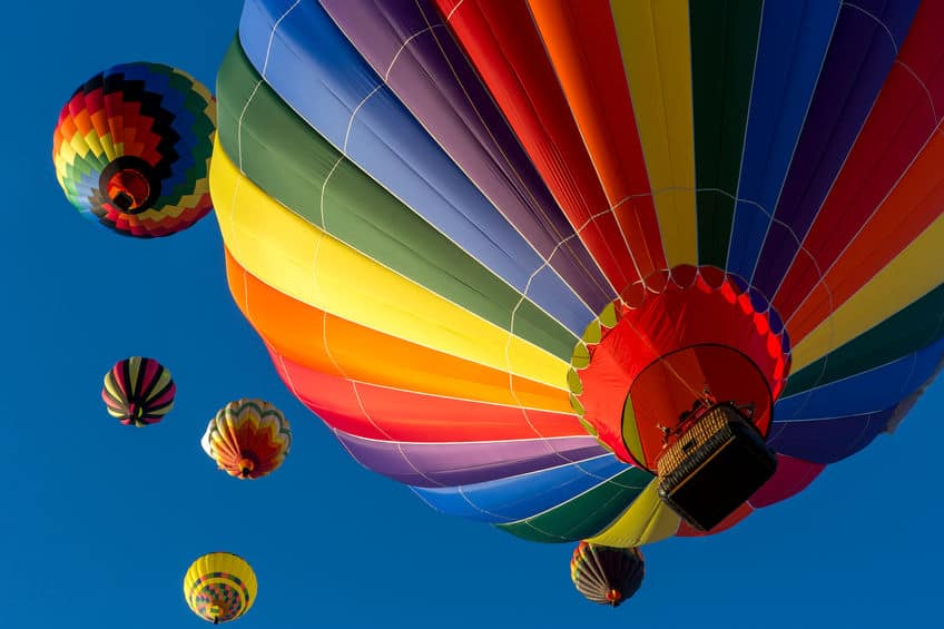 Colorful hot air balloons flying in the bright blue sky at the F>